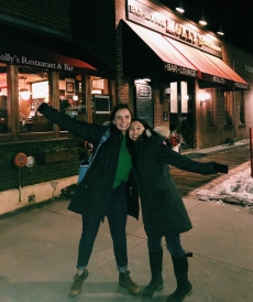 Abbi and her friend, Sarah, smile with their arms up in front of a classic, American style restaurant