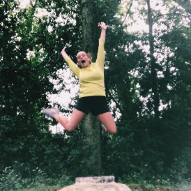 Abbi jumping in the middle of a forest in athletic gear.