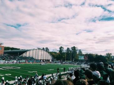 A view of the football field from the student section on a bright, fall day.