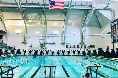 the empty Dartmouth pool with an American flag and championship banners hanging over it