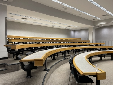 five rows of tables and chairs in a lecture hall with grey carpet and walls