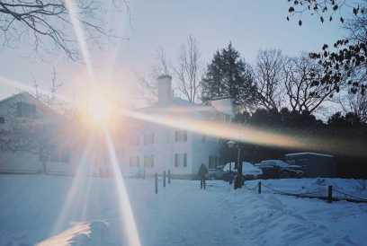 The sun rising in the background with a snowy path a white building in the foreground