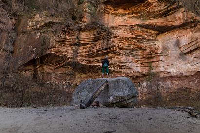 person facing rock cliff