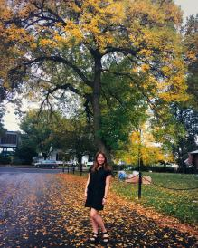 Autumn standing in front of fall tree