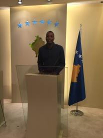 Jon at the podium outside the Kosovo Parliament room.