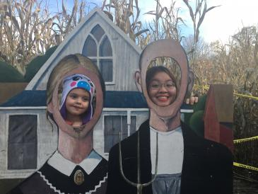 autumn and young girl poking heads through american gothic cutouts
