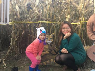 Autumn and young girl squatting in front of corn maze