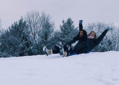 Abbi and a friend sharing a sled going down a snowy hill at the golf course.
