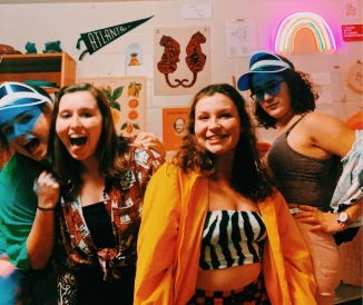 Abbi and 3 friends posing in very colorful attire in a dorm room