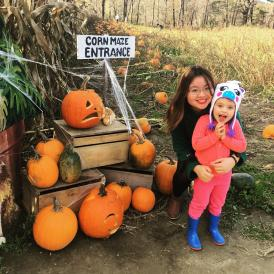 autumn posing with young girl in pumpkin patch