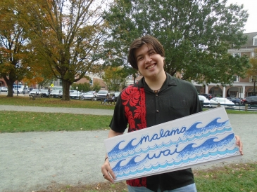 """Gabriel Gilbert '23 standing with """"Malama Wai"""" sign, dressed in black and red aloha shirt and light jeans"""