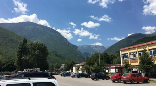 hospital peja kosovo yellow building cars mountains background