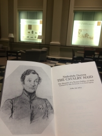 photo of book with illustration of woman in soldier's uniform; library backdrop