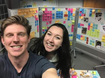 Colleen and her project partner, Matt, taking a selfie in front of their post-it note filled white boards