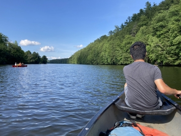 horizontal view of the connecticut river with a man paddling a canoe on the right