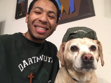 Tulio posing with his dog in a Dartmouth sweatshirt