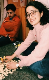 My friend, Jen, sitting on a dorm room floor in the middle of a bananagrams game