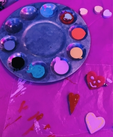 A paint palette, candy hearts, and painted clay hearts on top of a pink table clothe