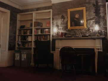 A room with a fireplace, black and white printed wall paper, and book shelves. There is also a portrait over the fireplace; everything seems old and elegant.