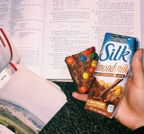 A hand holding a brownie and chocolate milk over a chemistry textbook and English book.
