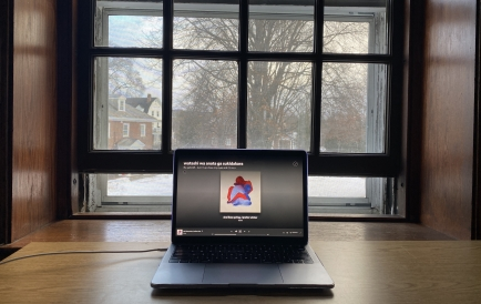 Picture of Gabriel's study setup, featuring a MacBook on a desk overlooking a snow-covered campus.