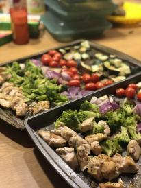 Rainbow vegetables and chicken on cookie sheet.