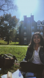 Abbi's friend sitting on the grass during an outdoor study session. A building and the sun are behind her.