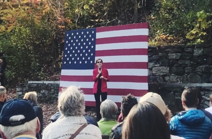 Sen. Warren speaking to a crowd outdoors, with an American flag in the background