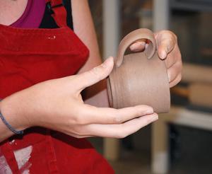 student holding ceramics cup