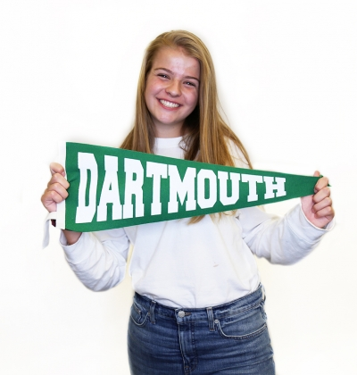 Student smiling holding Dartmouth banner