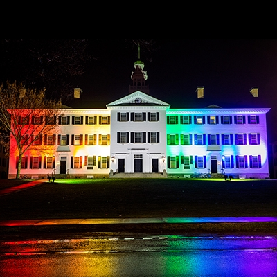 A photo of Dartmouth Hall at night, lit up with a rainbow of colors for the PRIDE celebration