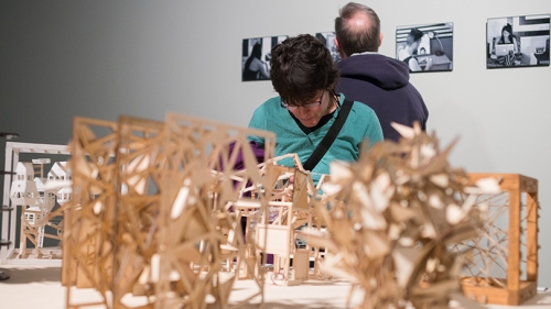 a person looking at 3 dimensional works of art cut from wood