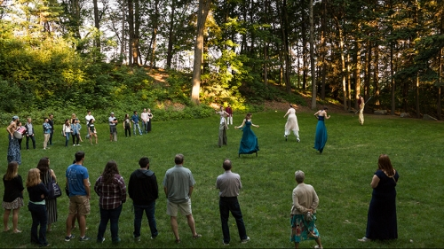 Actors on stilts rehearsing outside in a wooded area