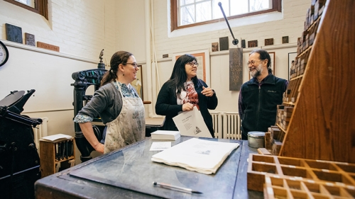 Sarah Smith, director of the Book Arts Workshop, and workshop participants Candessa Tehee and Ed Rayher demonstrate printing with Cherokee type in the Book Arts Workshop.