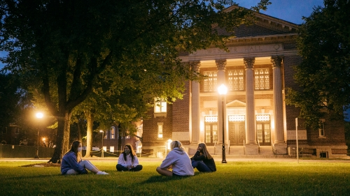 Masked students sitting on the Green at dusk across from Rauner Library