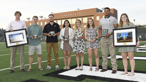 a group of students standing in a line on a football field holding awards