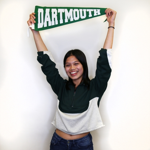 Student smiling for photo holding Dartmouth pennant over head