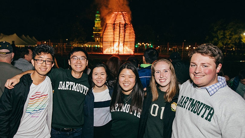 A photo of six Dartmouth alumni standing together in front of the Dartmouth Homecoming bonfire