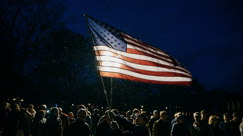 A photo of a person holding an American flag during a Veteran's Day ceremony