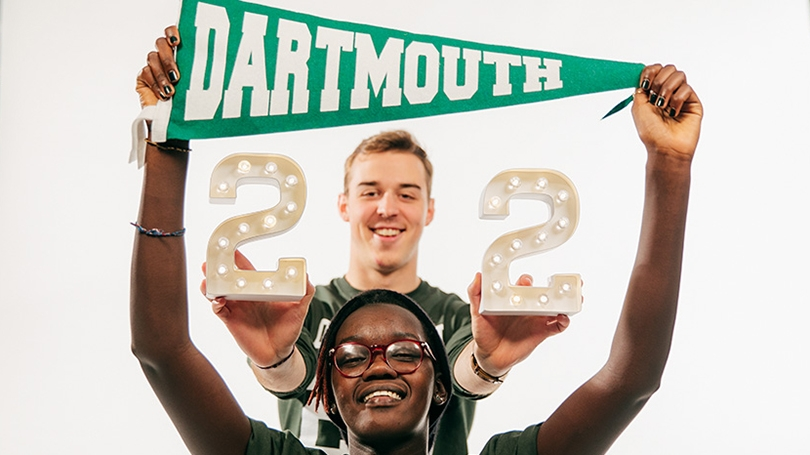 a female student holding a Dartmouth pennant above her head and a male student holding the number 22 behind her