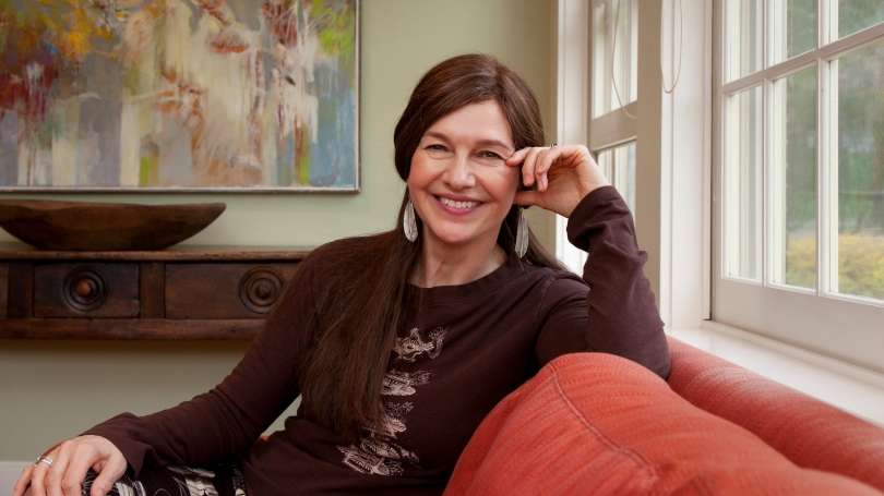 Louise Erdrich '76 sits on a couch at Dartmouth's Montgomery House