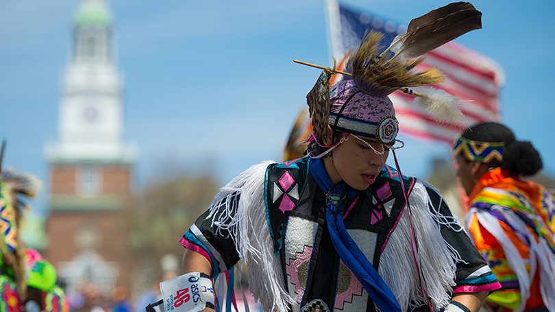 a Native American dancer in black and pink regalia with fringe and feathers