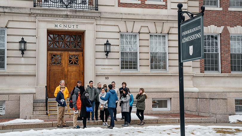 a group of prospective students gathered outside the admissions building at the start of a tour