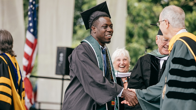 Theo Wilson in his graduation cap and gown shaking hands with President Phil Hanlon