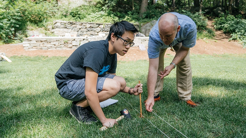 a student and professor placing string on the ground