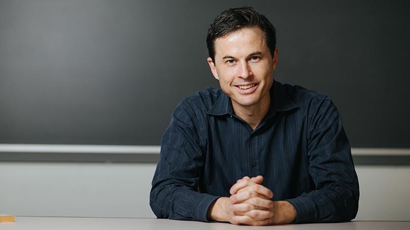 Brendan Nyhan sitting in front of a blank blackboard