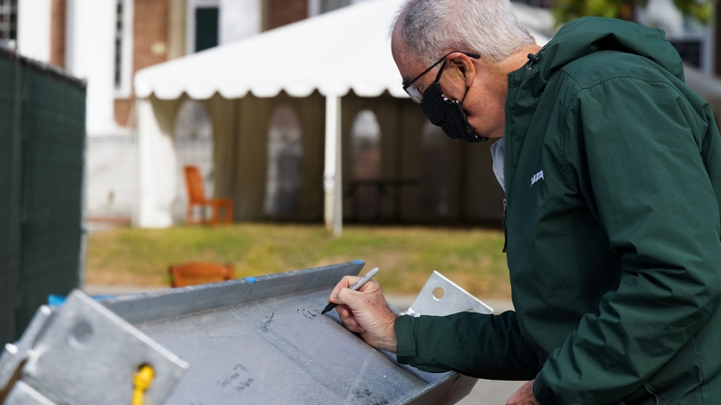 President Philip J. Hanlon '77 signs his name to the final beam.