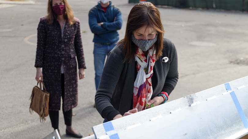 Professor of Environmental Sciences Elizabeth Wilson, the institute's founding director, signs the final beam.