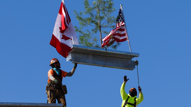 Culminating the topping-off ceremony, workers lower the beam into place.