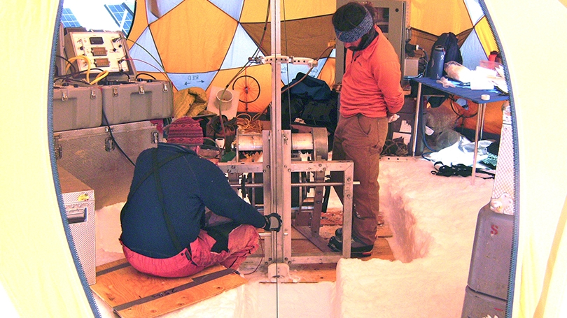 two men operating an ice drill under a tent